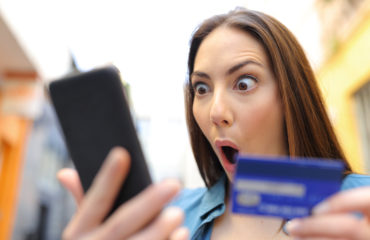Amazed woman buying with credit card finding discount on smart phone in the street